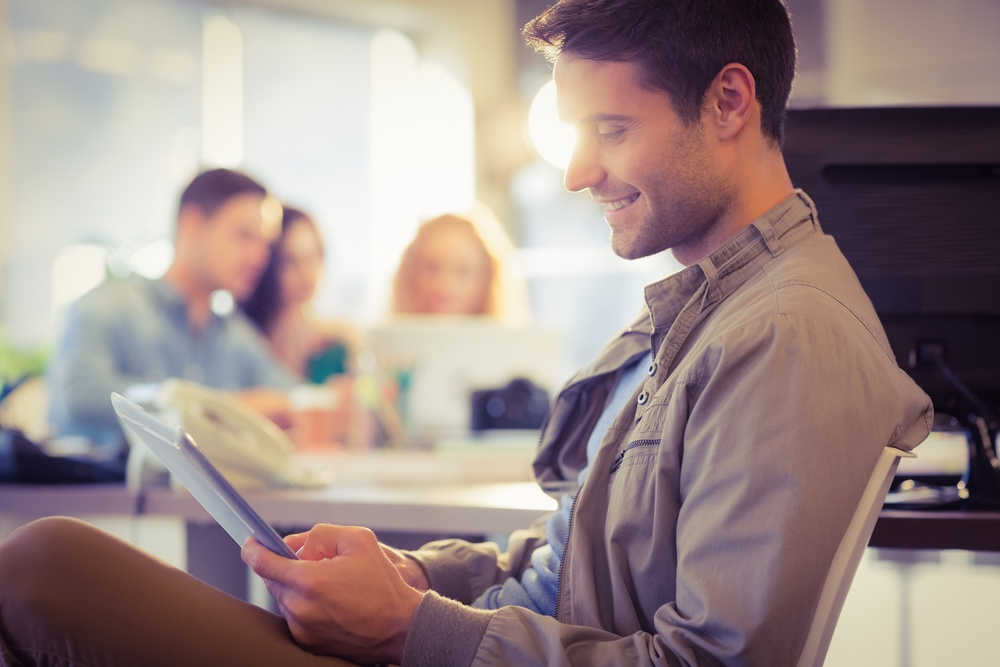 Smiling young man using digital tablet in the office.jpeg